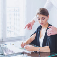 Sexual harassment at work, bosses hand on woman's shoulder