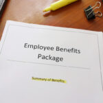Form that reads employee benefits package on a desk with surrounding office supplies