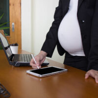 view of working pregnant worker on cellphone