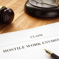 hostile work environment claim form next to gavel in court
