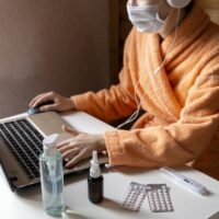 Woman with face mask working in cozy warm bath robe from home office surrounded by sanitizer, nasal drops,pills, thermometer. Ready for remote work on quarantine. Sick leave on remote online job