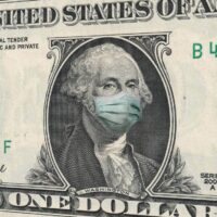 COVID-19 coronavirus in USA, ONE Dollar money bill with George Washington wearing healthcare surgical mask. Coronavirus in United States quarantine and global recession. Global economy hit by Covid19.