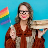 Young woman with books and LGBT flag