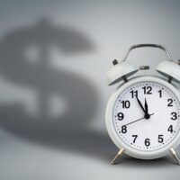 Alarm clock with dollar shadow, time is money concept